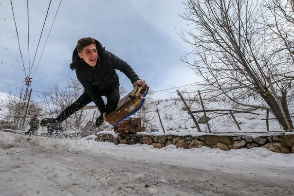 Парень катается на санках в городе Ван, Турция. Наши дни. Туда пришла  аномально холодная зима - даже снег выпал.