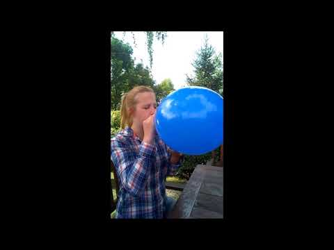 Blowing up a blue balloon until it pops in the garden as a challenge