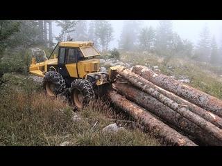 Skidder Ecotrac skidding big logs on rocky Mountain